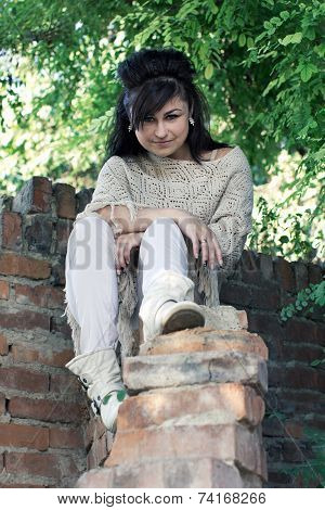 Girl Sitting On A Brick Wall