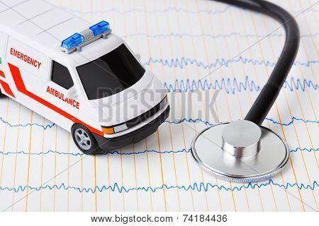 Stethoscope and ambulance car on ecg - medical background
