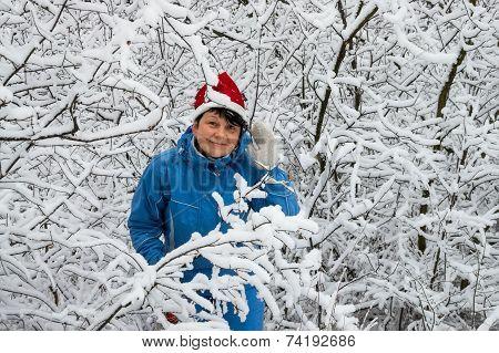 Woman In Ski Suit And Cap Of Santa Klaus  In Snow-covered Wood