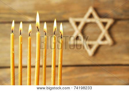 Hanukkah candle on wooden background