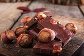 A stack of chocolate with hazelnuts on wooden table in warm style poster