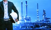 engineering man and safety helmet standing against oil refinery plant in heavy petrochemical industry estate poster