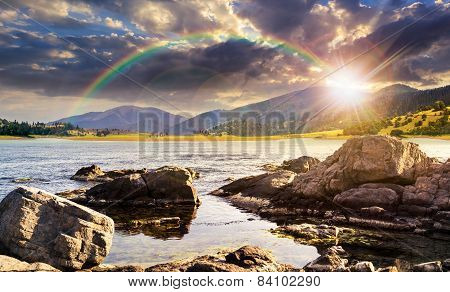 Lake With Boulders In Mountains At Sunset