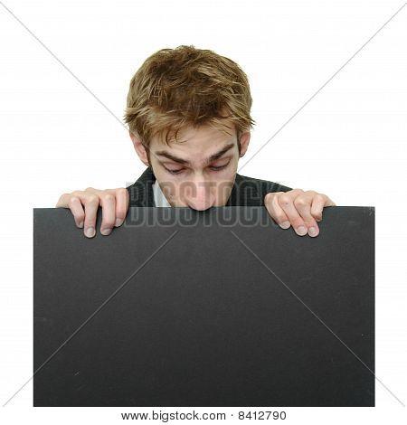 Businessman Peeking At Sign