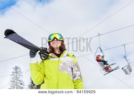 Happy woman in mask with ski lift behind her