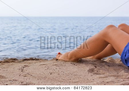 Legs of a young girl on a sandy beach