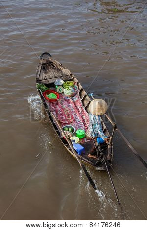 Woman on boat floating down Mekong river at Can Tho Floating Market