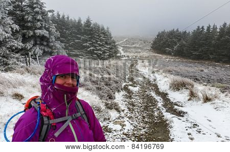 Woman Dressed In Winter Clothes Standing In A Winter Landscape