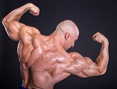 Bodybuilder is posing showing his muscles. Force relief muscle courage virility bodybuilder bodybuilding. The concept of a healthy lifestyle. poster
