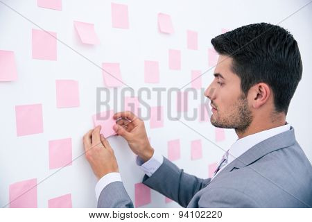 Businessman looking at sticker on wall in office