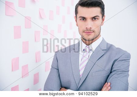 Handsome young businessman in suit standing in office and looking at camera