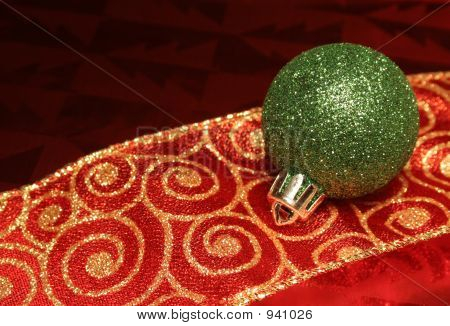 a sparkling green christmas ball ornament resting on a ribbon. poster