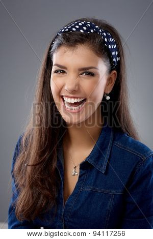 Attractive young woman laughing happy, looking at camera.