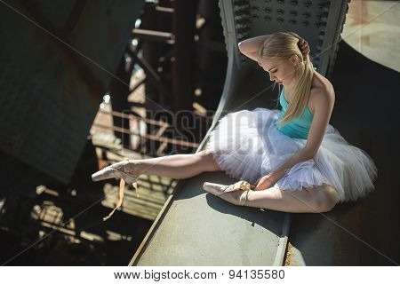 Ballerina sitting on the edge of bridge