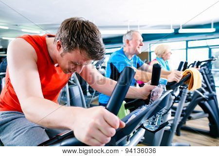 Sport in the gym - people spinning of fitness bikes, group of young and senior men and women