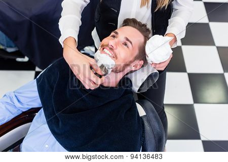 Man getting beard shave in barber salon poster