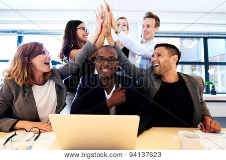 Group Of Executives High Fiving Over Colleague's Head