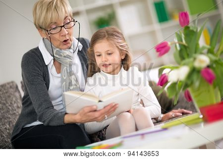 Grandmother reading interesting book her little granddaughter poster