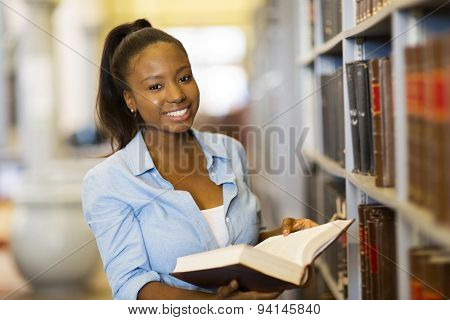 smiling female african american university student reading in library
