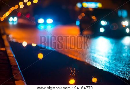 Night cityscape, lights reflected in the wet asphalt after rain.