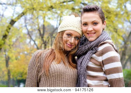 Two Beautiful Girlfriends Having Fun In The Park On Colorful Autumn Day