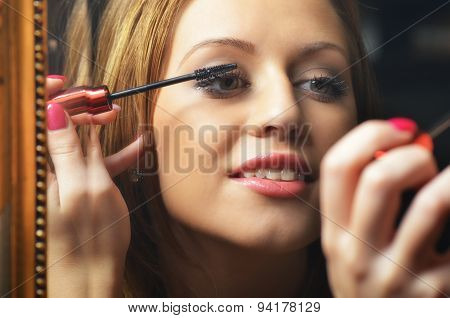Beautiful Young Woman Having Fun While Putting Make Up In Front Of The Old Mirror