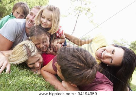 Two Families Playing In Park Together
