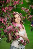 Young spring fashion woman in spring garden Springtime Summertime Trendy girl in the flowering trees in then at sunset in spring summer landscape background Allergic to pollen of flowers Allergy  poster