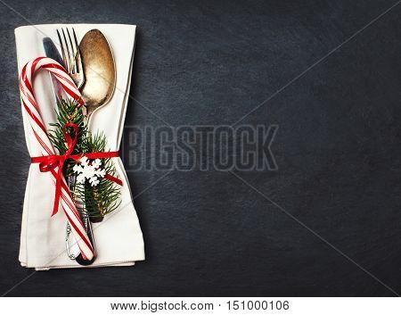 Christmas table place setting with christmas tree branches spoon knife fork and ribbon over black table with copyspace. Christmas holidays background