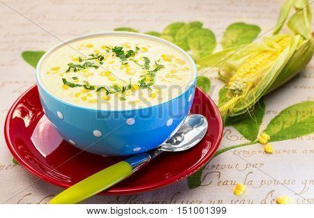 Bowl of corn soup cream on blue boul