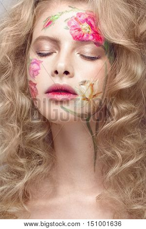 Beautiful blond girl with tresses and a floral pattern on the face. Beauty flowers. Portrait shot in studio