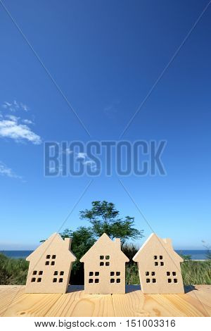 wooden toy house against clear blue sky background