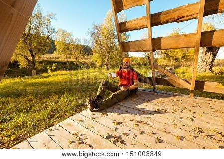 Young male traveling, resting in countryside sitting in hut of branches, with tourist rucksack, makes selfie, while enjoying nature view and summer rest