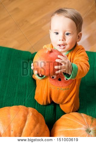 Happy smiling baby dressed as a pumpkin and a sincere look on the background of large orange pumpkins. The celebration of Halloween. Child holding a small pumpkin.
