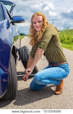 Young european woman changing car tire with road and rural landscape