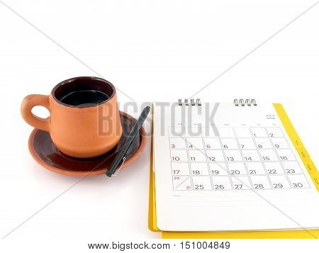 cup of coffee with saucer and desk calendar with days and dates in July 2016 isolated on white background, blank notes on calendar for monthly planning