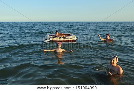 family with three children and a dinghy to play in summer