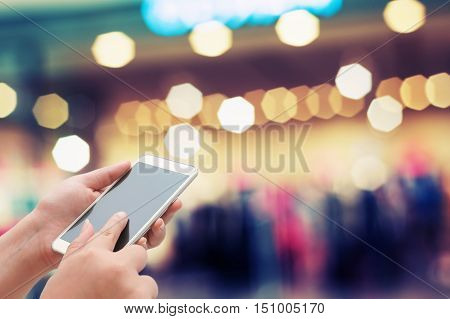 Women using Smart Phone on the night street with light bokeh background