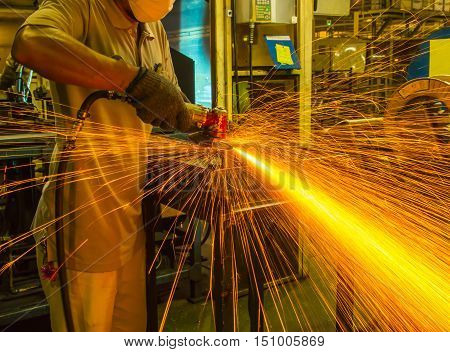 The worker grinding metal in manufacturing plant automotive part with fire spark