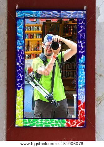 young photographer with a blue bandanna and a tripod makes a selfie in a mirror with decorated frame