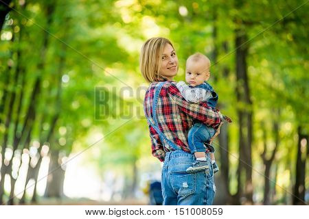 Cheerful young mother with her baby in her arms walks in the park in autumn. Happy kid mum on his hands in the park in autumn. A walk in the park with the baby in her arms. Happy mom.