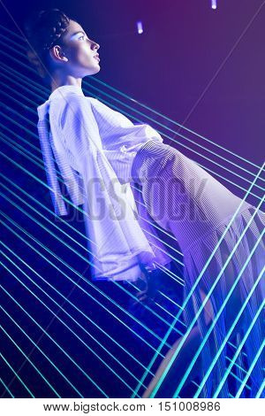 Fashion model beautiful girl in fashionable clothes in ultraviolet light, showing different poses. Beauty body and face. Photos shot in studio