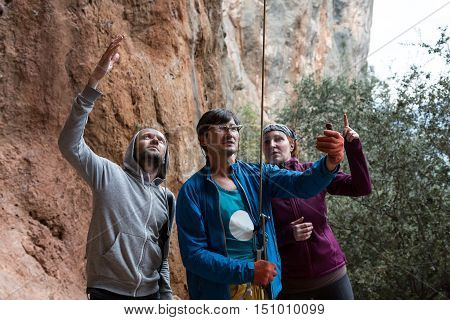 Mature Climbing Coach belays leading Athlete holding belay Device and Rope Man and Woman aside watching and making advices