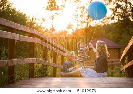 Mother with kid boy and cute little toddler sitting on wooden bridge and playing with blue balloon on summer sunset. Woman with children outdoors. Lifestyle concept