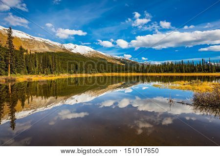 The concept of ecotourism. Sky and clouds reflected in the smooth water in the lake. Rocky Mountains on a sunny day