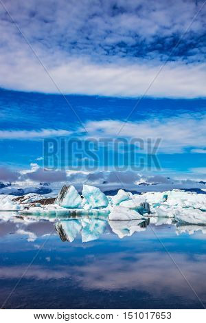 Ice floes and icebergs are reflected in the mirrored water of ocean. Ice lagoon in July. Summer vacation in Iceland