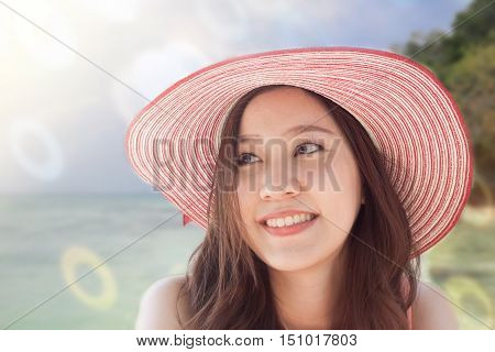 Close up beautifal Asian Woman wearing pink hat and smile with tropical sea background