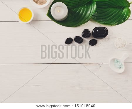 Spa treatment and aromatherapy top view background. Zen black stones, aroma salt, herbal balls for indian spa, candles, details and accessories for wellness beauty parlor. White wood with copy space