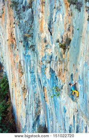 High vertical unusual orange and blue colors rocky Wall and solo male Climbers moving up