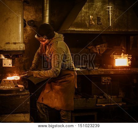 The blacksmith forging the molten metal on the power hammer in smithy.